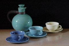 early_california_coffee_carafe_in_green_and_cups_and_saucers_in_dark_blue_and_light_blue_and_yellow